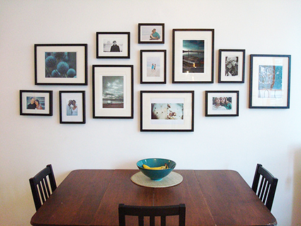 a lovely kitchen wall covered in framed photographs